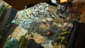This shows a closeup of the tulle holding little rocks...I stitch closely around the rocks and they are held in place by the tulle. This quilt is finished with a bound edge.  It has a sleeve on the top back edge for easy hanging with a dowel or curtain rod.